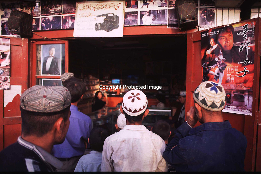 "HOTAn , 3 october 2001: young Uighur men watch a video at a local store in Hotan.Uighurs have their own idols and Chinese efforts to ""educate"" Uighurs have mostly failed.KASHGAR, SEPTEMBER 29 : Uighur muslim women walk in the bazaar in Kashgar.  Uighur muslims in China's western Xinjiang province mostly stick to islamic lifestyles due to their proximity to Afghanistan & Pakistan . Today, 47 percent of Xinjiang is Uighur and 41 percent is Han. Smaller groups of other Turkic Muslims, including Kyrgyz, Kazakhs, Tajiks and Uzbeks, make up the remainder of the population ..The government maintains tight control over Uighur culture.All mosques are required to register with the government. In 2001, authorities called in 8,000 imams for special training on the Communist Party's ethnic and religious policies. In 2002, Xinjiang's top university eliminated all instruction in the Uighur language. ... . .   . . .  . (photo by: katharina hesse/Grazia Neri)."