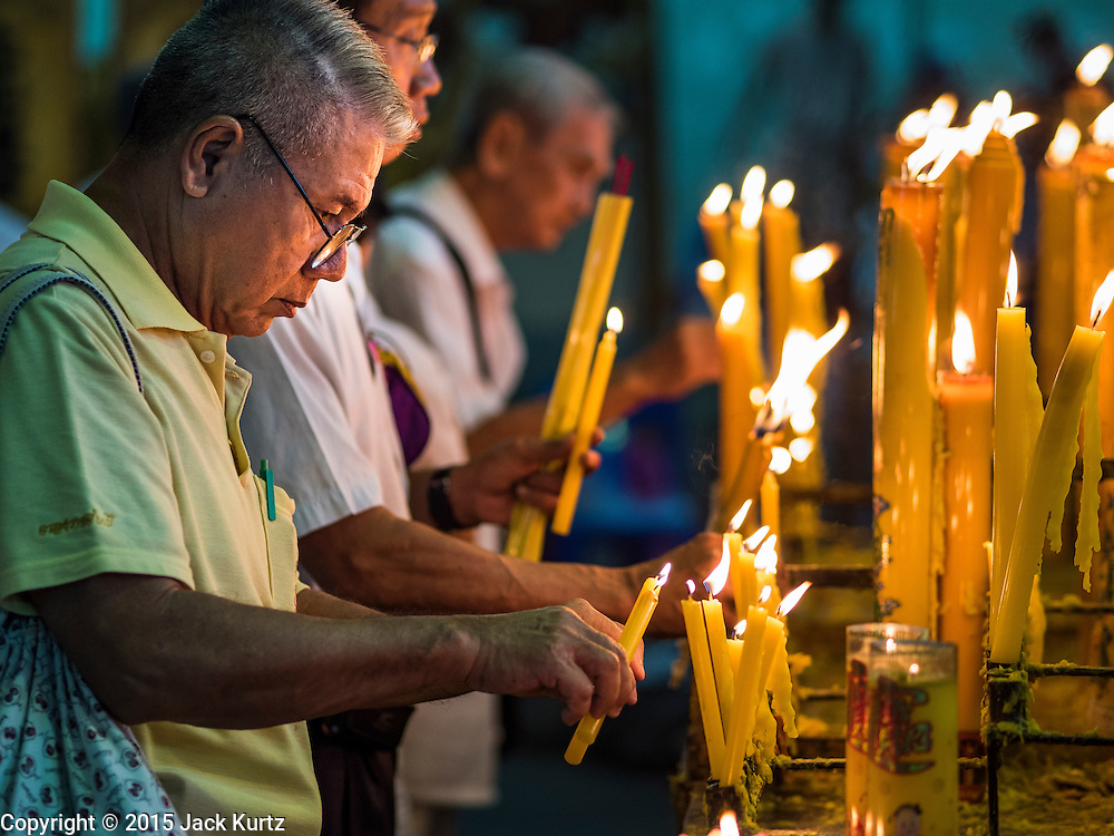 15 OCTOBER 2015 - BANGKOK, THAILAND: A man prays and lights candles during the Vegetarian Festival at the Joe Sue Kung Shrine in the Talat Noi neighborhood of Bangkok. The Vegetarian Festival is celebrated throughout Thailand. It is the Thai version of the The Nine Emperor Gods Festival, a nine-day Taoist celebration beginning on the eve of 9th lunar month of the Chinese calendar. During a period of nine days, those who are participating in the festival dress all in white and abstain from eating meat, poultry, seafood, and dairy products. Vendors and proprietors of restaurants indicate that vegetarian food is for sale by putting a yellow flag out with Thai characters for meatless written on it in red.    PHOTO BY JACK KURTZ