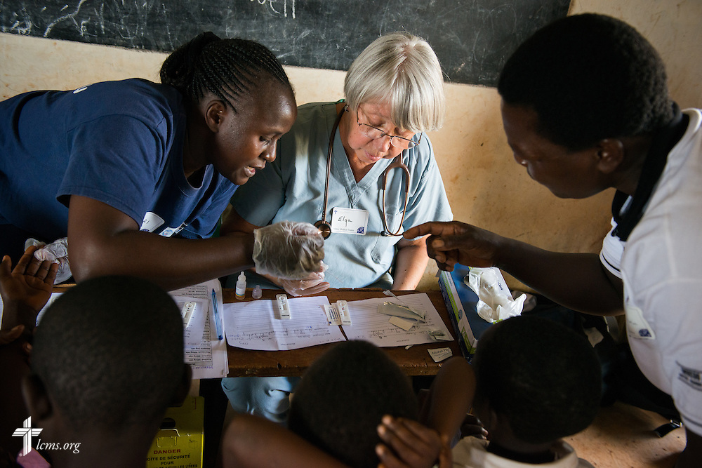 Elga Heintzen, a nurse from Hinsdale, Ill., attending First St. Paul Lutheran Church, works with Kenyan health workers to learn how to administer Malaria tests during the Mercy Medical Team clinic Wednesday, June 11, 2014, at the Luanda Doho Primary School in Kakmega County, Kenya. LCMS Communications/Erik M. Lunsford