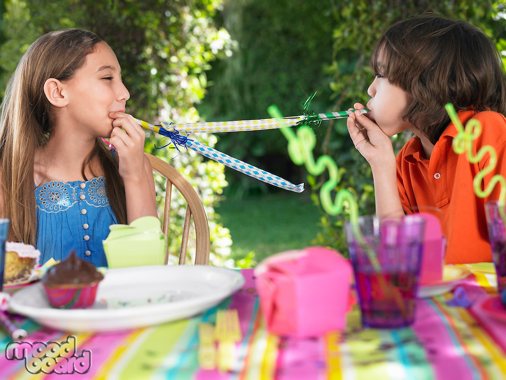 Two girls (10-12) blowing party puffers at birthday party