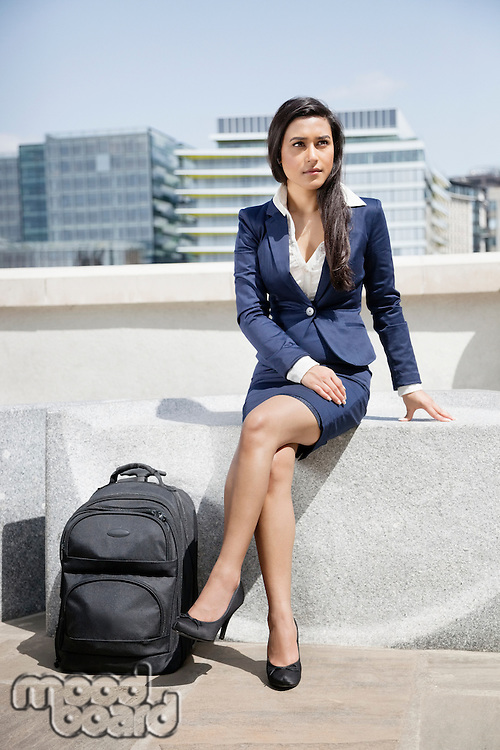 Young Indian businesswoman with luggage sitting outdoors