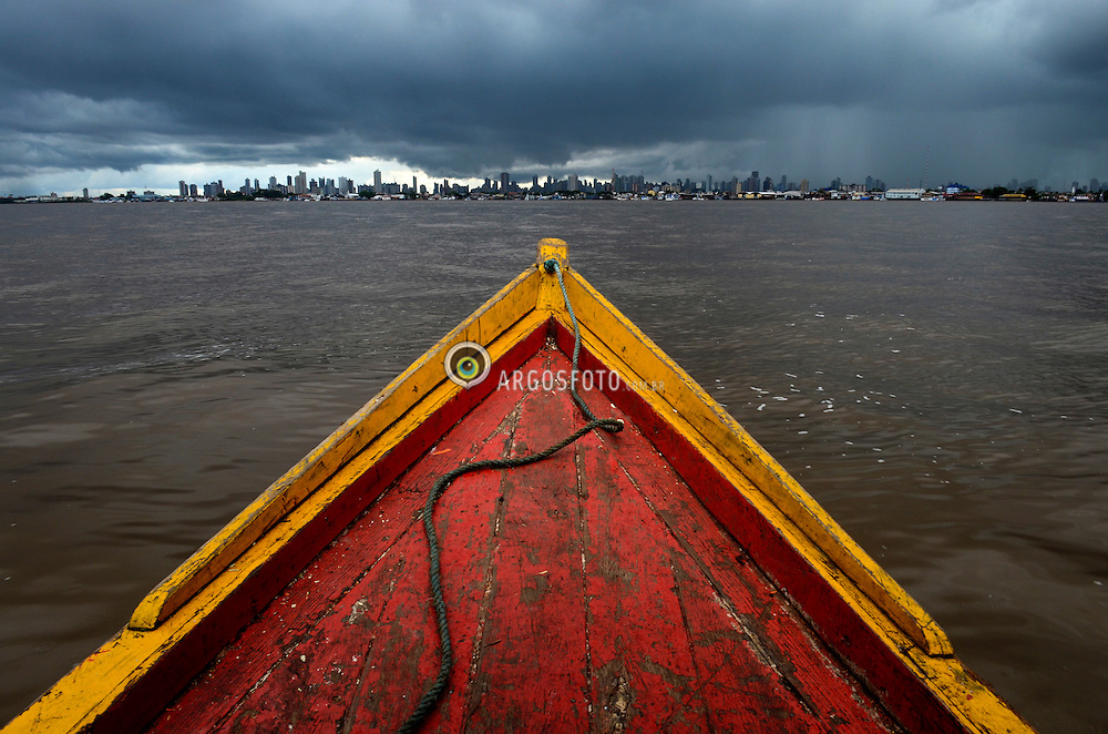 Proa de um barco popopo navegando pelo Rio Guama, tendo ao fundo uma tempestade que se forma em cima da cidade de Belem. // Prow of a popopo boat sailing the Guama river, against the background of a storm that forms over the city of Belem.  Foto: Carlão Limeira/Argosfoto - Belem, Para - Brazil - 2014
