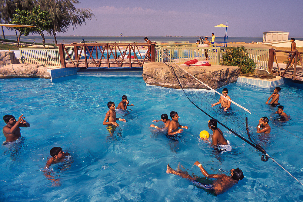 Umm al-Quwain, United Arab Emirates: Boys play volleyball at a waterpark popular with the local Indian community.