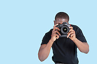 African American young man taking photo through digital camera over blue background