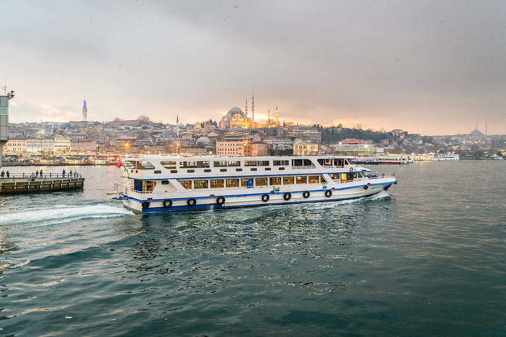 Ferry boat glides along Golden Horn with the bustling city of Istanbul, Turkey in the background