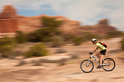 United States, Utah, Moab, female mountain biker riding through red rock canyon  MR
