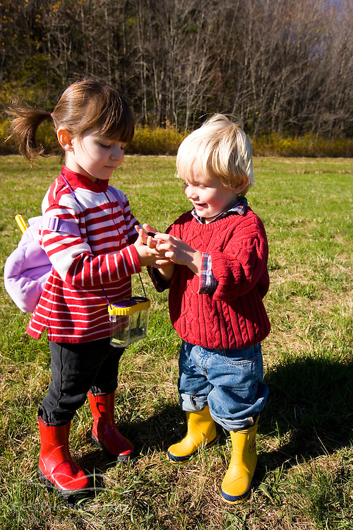 A young brother and sister look at a caterpillar in a field.  The Common Pasture in Newburyport, MA.