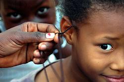Burkina Faso, Ouagadougou, 2007. Sisters help a young girl get hair extensions along a quiet Oaugadougou back street.