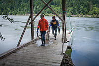 A Kim Brigham and daughter pull salmon from their gill nets on their families' platform.  Bonneville Dam in the background. Indian Fishers at Cascade Locks near Portland, Oregon fish for Salmon on platforms that have been in their family for generations.  The Indians are the only peoples with permits to fish this way on the Columbia River.  They sell fresh Salmon to buyers from the area.  They use traditional dip net and gill net fishing.
