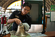 11 JULY 2011 - BANGKOK, THAILAND:   An employee of the State Railways of Thailand polishes a brass bell at his work station in Hua Lamphong train station in Bangkok. Hua Lamphong Grand Central Railway Station, officially known as the Bangkok Grand Central Terminal Railway Station, is the main railway station in Bangkok, Thailand. It is located in the center of the city in Pathum Wan District, and is operated by the State Railway of Thailand. The station was opened on 25 June 1916, after six years' construction. The station was built in an Italian Neo-Renaissance style, with decorated wooden roofs and stained glass windows. The architecture is attributed to Turin-born Mario Tamagno, who, with countryman Annibale Rigotti made a mark on early 20th century public building in Bangkok. The pair also designed Bang Khun Prom Palace (1906), Ananda Samakhom Throne Hall in The Royal Plaza (1907-15) and Suan Kularb Residential Hall and Throne Hall in Dusit Garden, among other buildings..There are 14 platforms and 26 ticket booths. Hua Lamphong serves over 130 trains and approximately 60,000 passengers each day. Thailand has the most advanced rail system in Southeast Asia and trains from Hua Lamphong serve all corners of the Kingdom.        PHOTO BY JACK KURTZ