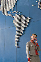 Business woman using mobile phone in front of world map in office
