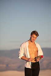 sexy young man with open shirt holding a single red rose outdoors