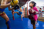 "18 DECEMBER 2104 - BANGKOK, THAILAND: A girl who wants to box works out with a boxer at the Kanisorn gym. The Kanisorn boxing gym is a small gym along the Wong Wian Yai - Samut Sakhon train tracks. Young people from the nearby communities come to the gym to learn Thai boxing. Muay Thai (Muai Thai) is a Thai fighting sport that uses stand-up striking along with various clinching techniques. It is sometimes known as ""the art of eight limbs"" because it is characterized by the combined use of fists, elbows, knees, shins, being associated with a good physical preparation that makes a full-contact fighter very efficient. Muay Thai became widespread internationally in the twentieth century, when practitioners defeated notable practitioners of other martial arts. A professional league is governed by the World Muay Thai Council. Muay Thai is frequently seen as a way out of poverty for young Thais and Muay Thai camps and schools are frequently crowded. Muay Thai professionals and champions are often celebrities in Thailand.     PHOTO BY JACK KURTZ"