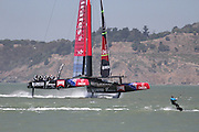 The Emirites Team New Zealand's boat practices for the America's Cup race while a kite surfer also catches some wind on the bay.
