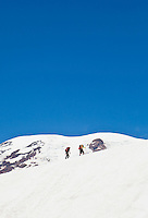 Two climbers make their way up the Muir snow field as they climb Mount Rainier, Washington, USA.