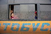 Saryarka street. School kids in a public bus.
