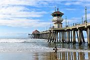 A Surfer Running on the Beach by the Huntington Beach Pier