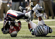 Joey Galloway (13) of the New England Patriots hangs on to a reception after colliding with Dwight Lowery of the New York Jets at Giants Stadium in E. Rutherford.