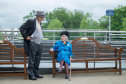 © Licensed to London News Pictures. 18/06/2014. Ascot, UK. A couple talk to each other.  Day two at Royal Ascot 18th June 2014. Royal Ascot has established itself as a national institution and the centrepiece of the British social calendar as well as being a stage for the best racehorses in the world. Photo credit : Stephen Simpson/LNP