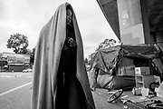A woman who goes by the name T walks towards a friend's tent near Northgate Avenue and Sycamore Street on Thursday, May 25, 2017, in Oakland, Calif. She was temporarily removed from her tent around the corner as Oakland officials cleared the street for cleaning. Nearly 70 percent of homeless people are black, although African Americans made up 28 percent of the city's 2010 census population.