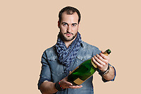 Portrait of a confident young man with champagne bottle over colored background