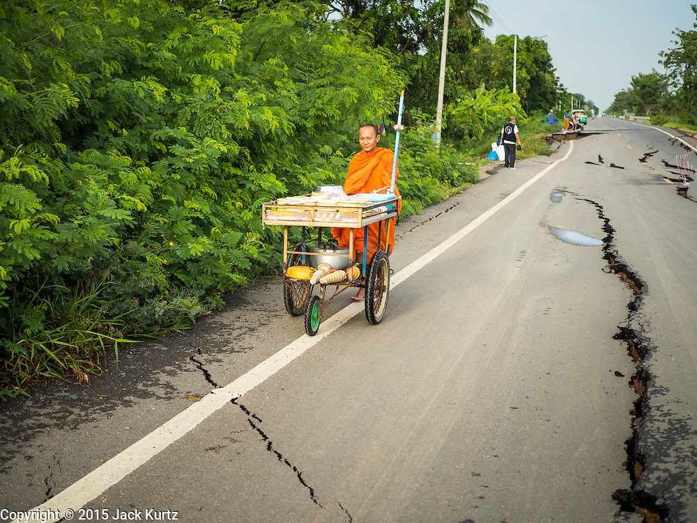 14 JULY 2015 - THAILAND: A Buddhist walks on damaged road in Pathum Thani province. The road bed collapsed because of subsidence. The drought that has crippled agriculture in central Thailand is now impacting residential areas near Bangkok. The Thai government is reporting that more than 250,000 homes in the provinces surrounding Bangkok have had their domestic water cut because the canals that supply water to local treatment plants were too low to feed the plants. Local government agencies and the Thai army are trucking water to impacted communities and homes. Roads in the area have started collapsing because of subsidence caused by the retreating waters. Central Thailand is contending with drought. By one estimate, about 80 percent of Thailand's agricultural land is in drought like conditions and farmers have been told to stop planting new acreage of rice, the area's principal cash crop.       PHOTO BY JACK KURTZ