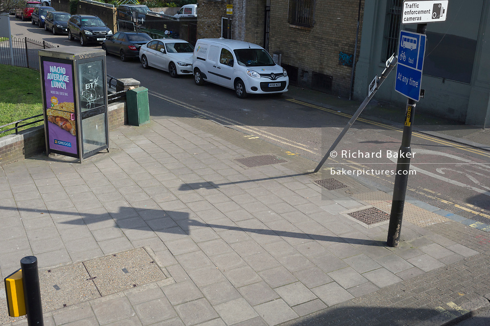 A leaning post and its slanted shadow on the Walworth Road in Southwark, on 28th March 2019, in London, England