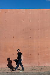 man walking by a modern wall in New Mexico