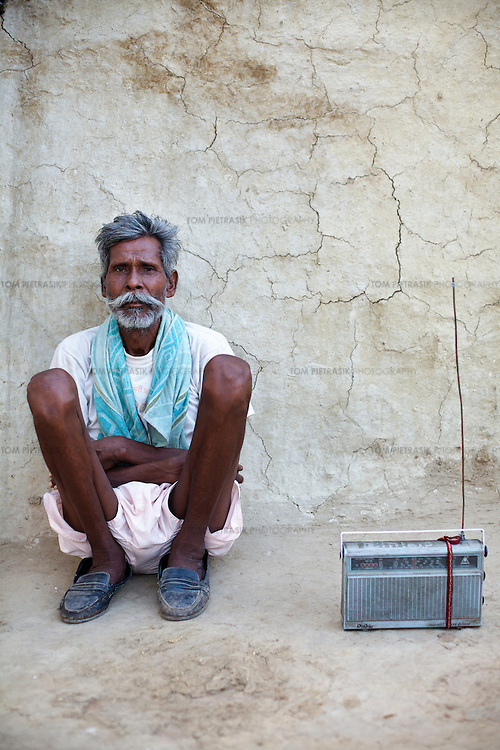 A man from the Adivasi (tribal, or Scheduled Tribe) village of Patara, 20km from Shivpuri, listens to a radio outside his home. A survey recently found that half of all adult Adivasi residents in Shivpuri listen to the radio several times over the course of a day. The Adivasis are traditionally ostracised and many of them are illiterate so rely on the radio for news, information and entertainment. ..Shivpuri district in Madhya Pradesh suffers from poor health outcomes. Of particular concern is the high rate of maternal mortality. One of the Indian government's aims, with partners Unicef, is to encourage the population to adopt practices to improve sanitation and health practices. In an area made up of traditionally disadvantage groups and suffering low literacy rates, this can be a challenge. ..A survey found that radio was the most readily accessible media by the Shivpuri community with more than half saying they tuned in several times a day. ..Dharkan 107.8 FM will go on air in July. The station that will broadcast to 75 villages in a 15-kilometer radius reaching 170,000 people...Rather than preaching educational messages, the station, which is already producing pilot programs, uses humor and folk artists performing in the local language to entertain and inform their audiences. There is a major impact, especially on women, who are contributing their voices to such wide-ranging issues as caste discrimination, female feticide and women,A?o?s empowerment. ..Photo: Tom Pietrasik.Shivpuri, Madhya Pradeh. India.June 2009