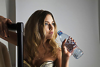 Fashion model drinking water from bottle in studio