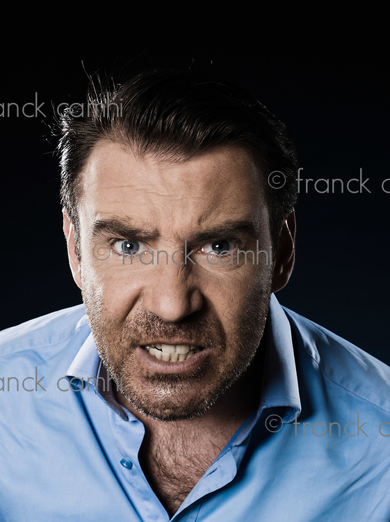 caucasian man unshaven pucker angry portrait isolated studio on black background