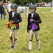 Young riders at the horse show, with ribbons.<br />