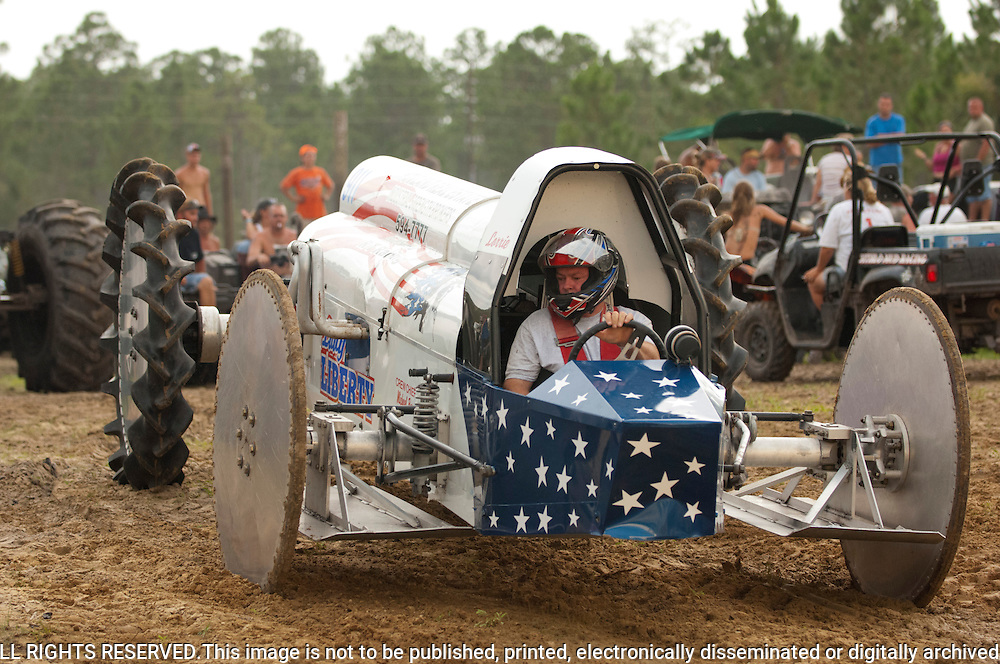 "The Redneck Yacht Club was the 4th of July holiday destination for mudders and swampbuggy enthusiasts. The holiday drew several thousand...Randy Johns of Naples, FL, driving the ""Lady Liberty"" V8 super stock swamp buggy, hurls down the straightaway on the mud track racing oval. He built the rig for his wife, Lorrie, who also races. With no other contestants in that class, this was an exhibition run...©Rich Frishman.ALL RIGHTS RESERVED.This image is not to be published, printed, electronically disseminated or digitally archived without expressed written permission of the photographer...contact info:.Rich Frishman.PO Box 1213; Langley WA 98260  USA.360-221-1984 (studio phone).rich@frishphoto.com (e-mail).http://www.richfrishman.com.http://www.frishphoto.com"