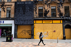 Glasgow, Scotland, UK. 12 June 2020.  Although shops can reopen in England next week, in Scotland the lockdown is not being relaxed so quickly with several more weeks of restrictions to go. Shops and businesses remain closed and streets are very quiet. Pictured; woman walks past closed Princes Square on Buchanan Street. Iain Masterton/Alamy Live News