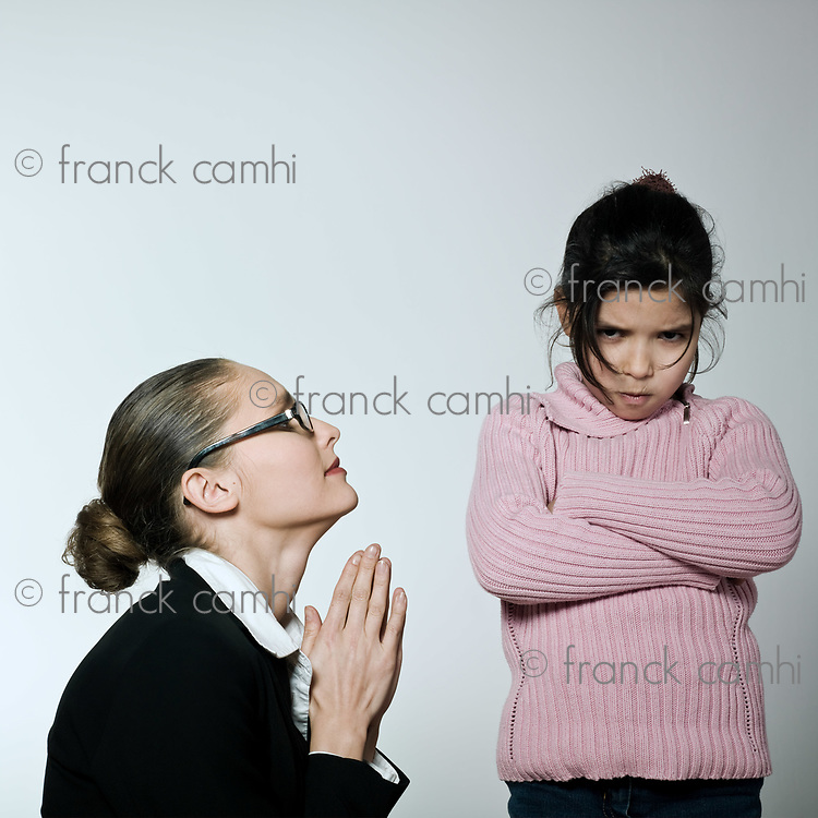 studio shot of a young woman having problem educate knelling and begging her child on studio isolated backgroun