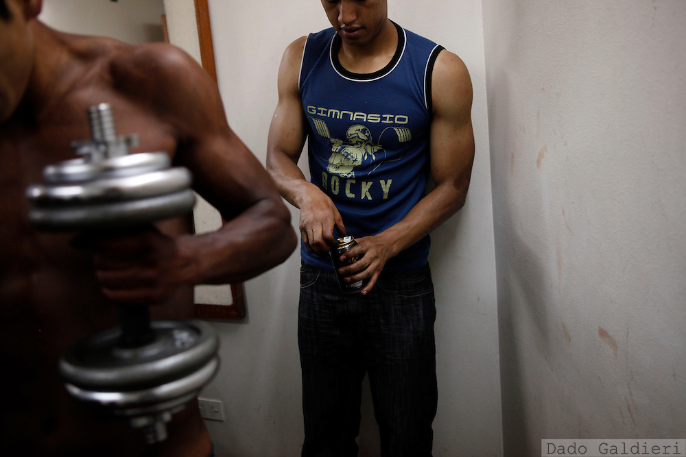 A bodybuilder warms up, left, as another opens an energy drink before competing in a regional bodybuilding championship in La Paz, Saturday, April 10, 2010.