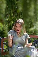 Surprised young woman reading text message on smart phone in park