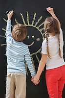 Back view of siblings drawing sun on blackboard while holding hands