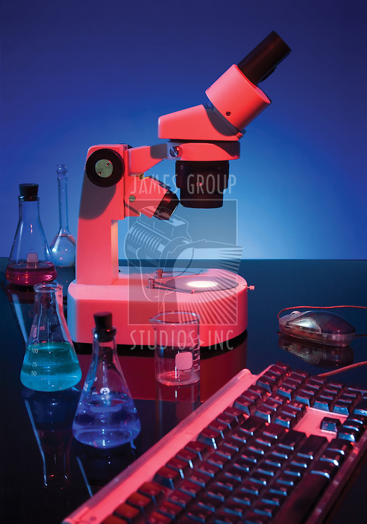 Stereoscopic microscope, chemistry flasks and computer keyboard on blue background