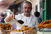 TETOUAN, MOROCCO - 5th April 2016 - A street food vendor prepares Moroccan chebekia and birouat street food at his stall in the Tetouan Medina, Rif region of Northern Morocco.
