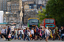 Busy pedestrian crossing at Princes Street with Old town in background during Edinburgh Festival, Edinburgh, Scotland, UK