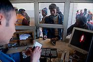 Les réfugiés présentent leur Passeports aux autorités Tunisiennes, poste frontière de Ras Jedir. Plus de 140 000 réfugiés ont déjà quitté la Libye par la Tunisie ou l'Egypte et des milliers continuent d'arriver chaque jours. Mercredi 2 Mars 2011, poste frontière de Ras Jedir, Tunisie..© Benjamin Girette / AP