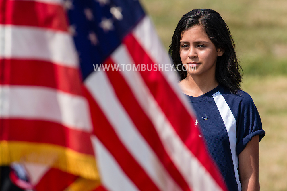 New Windsor, New York - A female teenager stands at attention during A U.S. Air Force oath of enlistment ceremony on the first day of the New York Air Show at Stewart International Airport on Aug. 29, 2015. ©Tom Bushey / The Image Works
