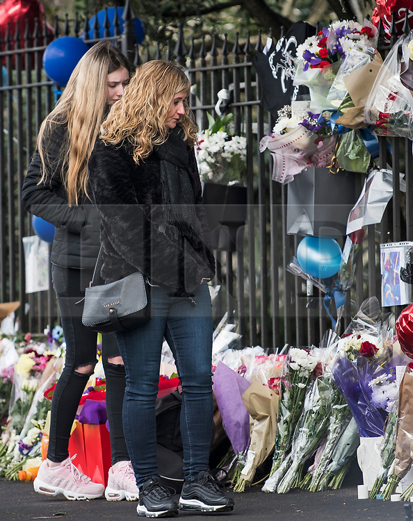 © Licensed to London News Pictures. 28/01/2018. London, UK. Two women look at tributes left at the scene where three teenage pedestrians were killed near a bus stop in Hayes, West London when a black Audi collided with them. Named locally as Harry Rice, Josh Kennedy and George Wilkinson, the three teenagers were hit on Friday night  close to the M4 Junction 4. A 28-year-old man has been arrested and a police are currently looking for a  second man believed to have been in the Audi.. Photo credit: Ben Cawthra/LNP