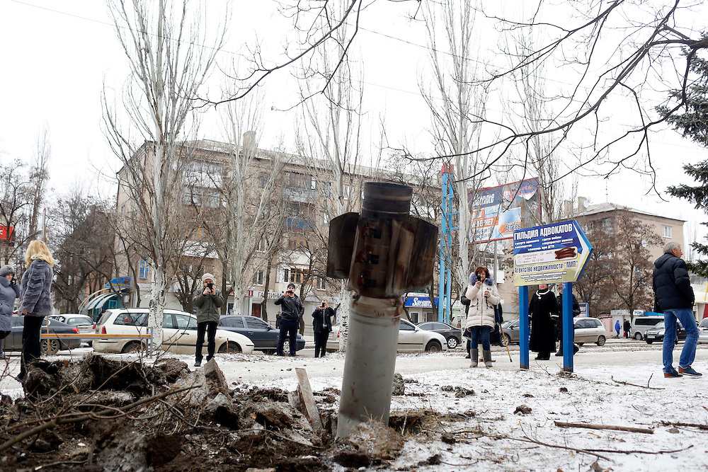 People photograph an apparently unexploded shell that lodged in the ground near Dvirtseva Street after numerous shells hit the city center and surrounding area on February 10, 2015 in Kramatorsk, Donetsk Oblast, Ukraine.
