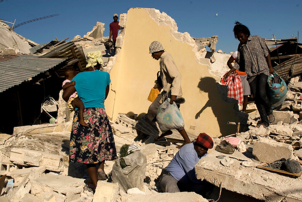 Residents stand outside earthquake-damaged buildings on January 14, 2010, in the Fort National neighborhood of  Port-au-Prince, Haiti.  Destruction has devastated Port-au-Prince and much of the country of Haiti following a massive earthquake that has killed thousands.