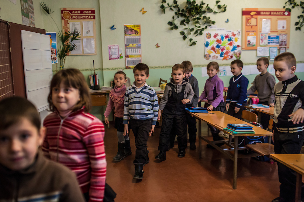 MARIUPOL, UKRAINE - FEBRUARY 6, 2015: Students at School 68 take part in a drill in which they pratice what to do in case of shelling in Mariupol, Ukraine. On January 24, shelling just nearby killed 31 people and injured over 100, prompting the school to increase the frequency of the drills to daily instead of weekly. CREDIT: Brendan Hoffman for The New York Times