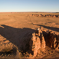 USA, Utah, Hanksville, Setting sun lights red sandstone mesas on autumn evening
