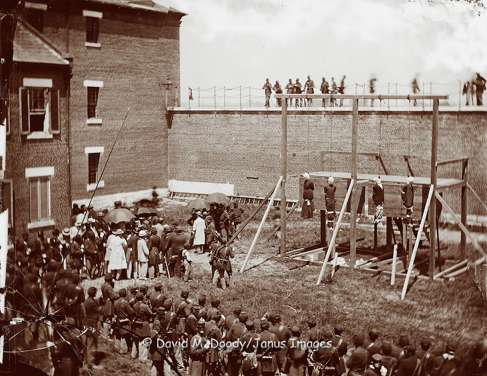 Washington, D.C. Hanging hooded bodies of the four conspirators; crowd departing.  Washington 1865, the assassination of President Lincoln, April-July 1865. Photograph includes woman being executed, 1865 July 7.   Photo by Alexander Gardner, (1821-1882,).United States--History--Civil War, 1861-1865--Military facilities..Surratt, Mary E..Payne, Lewis..Herold, David E..Atzerodt, George A..Lincoln, Abraham,--1809-1865.--Assassination..Armories..Hangings..United States--District of Columbia--Washington..