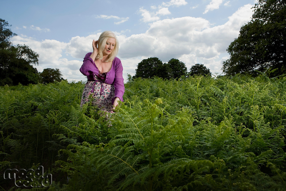 Woman Walking in a Meadow of Ferns